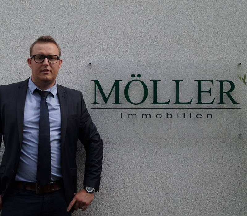 Immobilienmakler Alexander Möller vor Büro